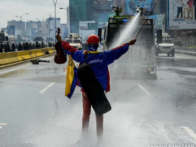 Opposition activist Wuilly Arteaga stands with a violin in front of an armoured vehicle of the riot police during a protest against President Nicolas Maduro in Caracas, on May 24, 2017. Venezuela's President Nicolas Maduro formally launched moves to rewrite the constitution on Tuesday, defying opponents who accuse him of …