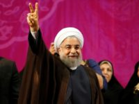 Iranian President Hassan Rouhani, who has comfortably won a second term, gestures during a campaign rally in Tehran on May 9, 2017