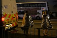Concert goers wait to be picked up after a suspected terror attack during a pop concert by Ariana Grande in the northern English city of Manchester