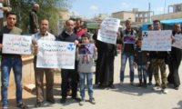 Syrian residents of Khan Sheikhun hold placards and pictures on April 7, 2017 during a protest condemning a suspected chemical weapons attack on their town