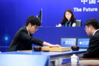 China's 19-year-old Go player Ke Jie (L) makes a move during the first match against Google's artificial intelligence programme AlphaGo