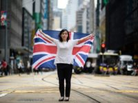 Designer Alice Lai, 39, holds a British Union Jack flag on a main road in Hong Kong. Almost 20 years after the city was handed back to China, colonial emblems have become a symbol of protest