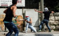 Palestinian protesters use slingshots to hurl stones towards Israeli security forces during clashes in the West Bank town of Bethlehem on April 21, 2017, in solidarity with the hunger striking prisoners