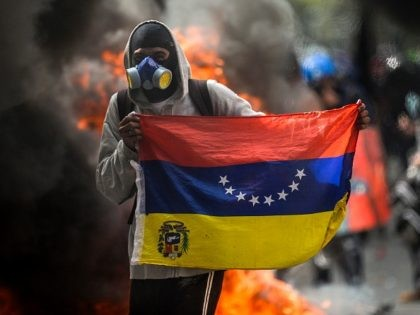 A hooded demonstrator holds a national flag near a burning motorbike during a protest against the government of President Nicolas Maduro in Caracas on May 31, 2017. Venezuelan authorities on Wednesday began signing up candidates for a planned constitutional reform body, a move that has inflamed deadly unrest stemming from …