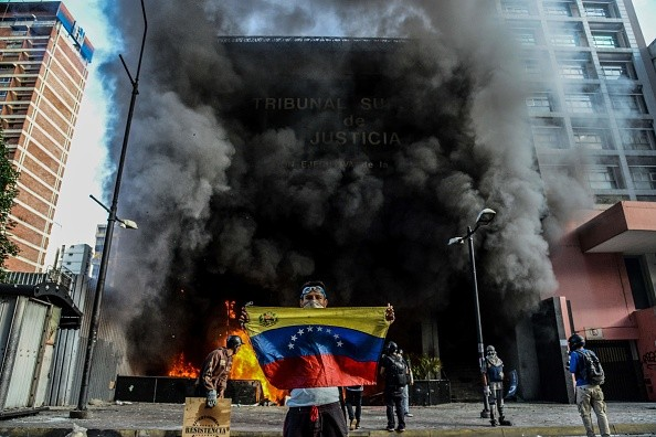 TOPSHOT - Anti-government demonstrators attack the administration headquarters of the Supreme Court of Justice as part of protests against President Nicolas Maduro in Caracas, on June 12, 2017. With Venezuelans suffering from high inflation, food shortages and soaring crime rates, plus a deepening corruption scandal, the Venezuelan opposition has mounted …