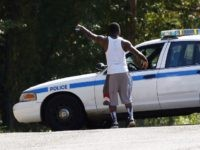 A resident gestures to a policeman as a police presence remains in a south Jackson, Miss., neighborhood, Thursday, Sept. 22, 2016, while lawmen continue to negotiate with a man suspected of holding about a dozen people against their will. Authorities believe all the hostages have been safely removed without a …