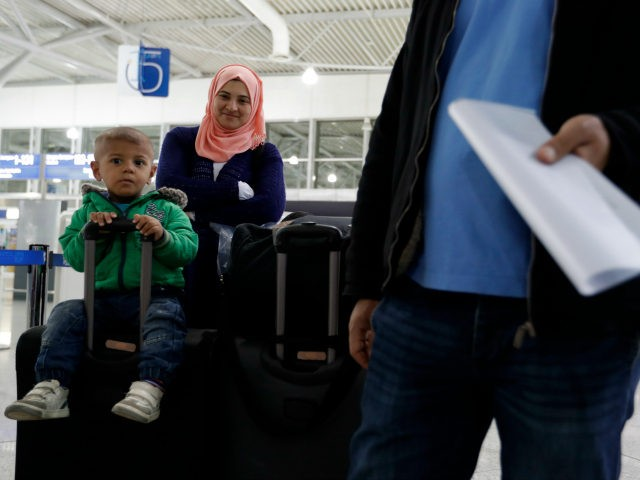 Syrian refugee Sumeya Akdrou smiles as she looks at her youngest son Elias sitting on a suitcase at the Athens airport before taking a flight to Madrid on Monday, Sept. 26, 2016. A group of 27 Syrians and four Iraqis was among the very few accepted by a European country …