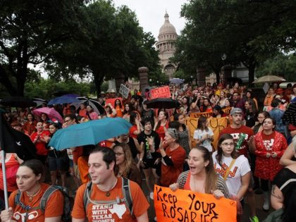Abortion rights demonstrators rally outside of the State Capitol to protest recent legislation that could shut down all but five clinics and restrict abortion rights throughout the state in Austin, Texas on Monday, July 15, 2013. (AP Photo/Tamir Kalifa)