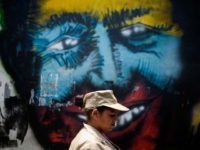 TOPSHOT - A Bolivarian militia member walks by a graffiti of the late Venezuelan President Hugo Chavez during a rally to commemorate 15 years of the coup that briefly removed him from power, in Caracas on April 11, 2017. The last week has been marked by street protests called by …