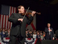 "Luis Haza plays the US National Anthem as US President Donald Trump (R) listens at the Manuel Artime Theater in Miami, Florida, on June 16, 2017. Trump denounced Raul Castro's ""brutal"" Cuban regime on Friday in a speech to Cuban-American exiles vowing to restore ""freedom"" to their homeland. / AFP …"