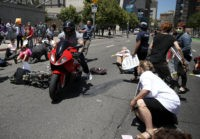 SAN FRANCISCO, CA - JUNE 21: A motorcyclist rides through dozens of healthcare activists who were blocking a street while staging a die-in as the protested the Trumpcare bill on June 21, 2017 in San Francisco, California. The man narrowly missed the protesters on Seventh Street. Dozens of healthcare activists …