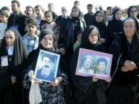 Kurds holds pictures of dead relatives during the anniversary ceremony at the memorial site of the 1988 victims of a gassing in the Kurdish town of Halabja, 300 kms (190 miles) northeast of Baghdad 16 March 2005. On March 16, 1988, the forces of then President Saddam Hussein dropped chemical …