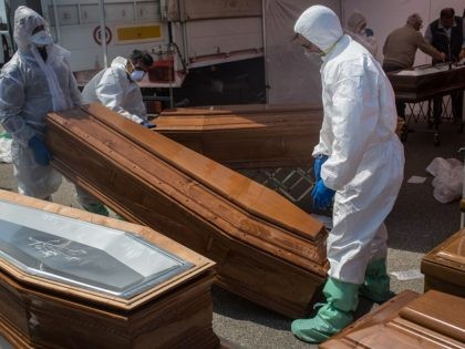 """CROTONE, ITALY - MAY 27: Members of the Italian Red Cross prepare coffins for the 34 migrants that died at sea on May 24 after the Migrant Offshore Aid Station (MOAS) """"Phoenix"""" vessel disembarked more than 600 people on May 27, 2017 in Crotone, Italy. More than 600 refugees and …"""
