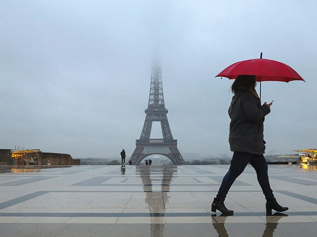People with umbrellas walk on the human rights plaza in front of the Eiffel tower during a rainy morning in Paris on February 7, 2017. / AFP / Ludovic MARIN (Photo credit should read LUDOVIC MARIN/AFP/Getty Images)