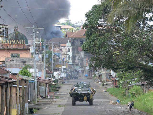 In this file photo, a Philippine Marines armored personnel carrier speeds away as black smoke billows from burning houses after military helicopters fired rockets at militant positions in Marawi City on May 30, 2017. File photo by Ted Aljibe/AFP