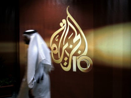 FILE -- In this Nov. 1, 2006 file photo, a Qatari employee of Al Jazeera Arabic language TV news channel walks past the logo of Al Jazeera in Doha, Qatar. Hackers allegedly broke into the website of Qatar's state-run news agency and published a fake story quoting the ruling emir, …