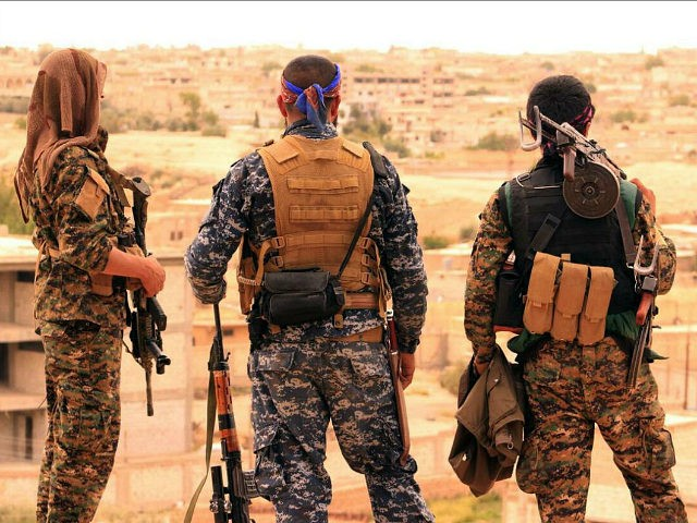 FILE -- This April 30, 2017, file photo, provided by the Syrian Democratic Forces (SDF), shows fighters from the SDF looking toward the northern town of Tabqa, Syria. U.S.-backed Syrian forces have launched their attack on the Islamic State group's de facto capital of Raqqa, in northern Syria, just as the jihadist group is making its last stand in Mosul in neighboring Iraq.. (Syrian Democratic Forces, via AP, File)