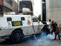 TOPSHOT - A Venezuelan National Guard riot control vehicle runs over an opposition demonstrator during a protest against Venezuelan President Nicolas Maduro, in Caracas on May 3, 2017. Venezuela's angry opposition rallied Wednesday vowing huge street protests against President Nicolas Maduro's plan to rewrite the constitution and accusing him of dodging elections to cling to power despite deadly unrest. / AFP PHOTO / FEDERICO PARRA (Photo credit should read FEDERICO PARRA/AFP/Getty Images)