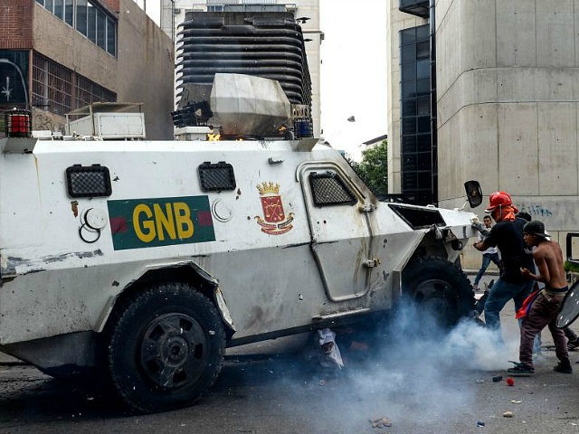 TOPSHOT - A Venezuelan National Guard riot control vehicle runs over an opposition demonstrator during a protest against Venezuelan President Nicolas Maduro, in Caracas on May 3, 2017. Venezuela's angry opposition rallied Wednesday vowing huge street protests against President Nicolas Maduro's plan to rewrite the constitution and accusing him of …