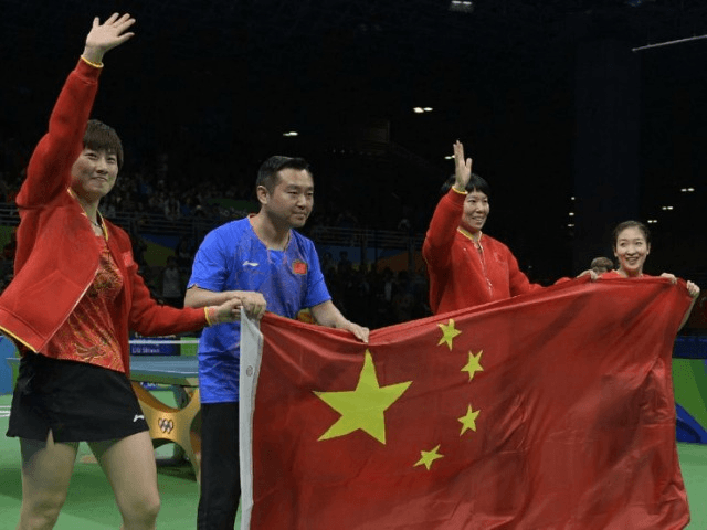 (L-R) China's Ding Ning, coach Kong Linghui, Li Xiaoxia and Liu Shiwen posing with the national Chinese flag after winning gold medals in the women's team final table tennis at the Riocentro venue during the Rio 2016 Olympic Games in Rio de Janeiro