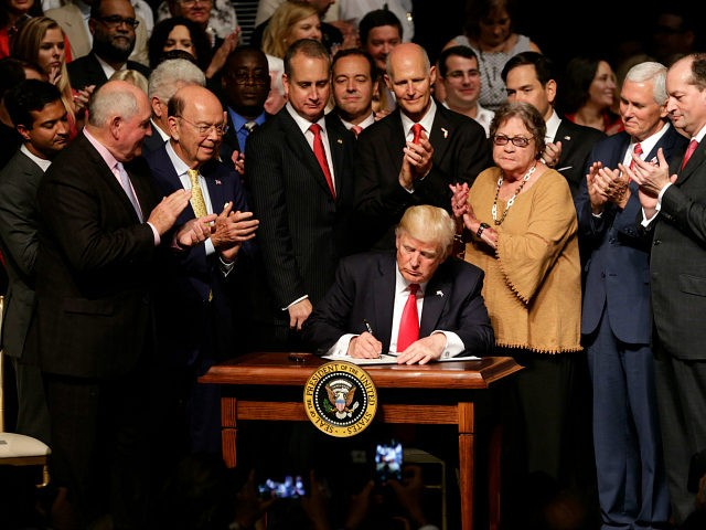 President Donald Trump signs an executive order on a revised Cuba policy aimed at stopping the flow of U.S. cash to the country's military and security services while maintaining diplomatic relations, Friday, June 16, 2017, in Miami. From left are, Agriculture Secretary Sonny Perdue, Commerce Secretary Wilbur Ross, Rep. Mario …