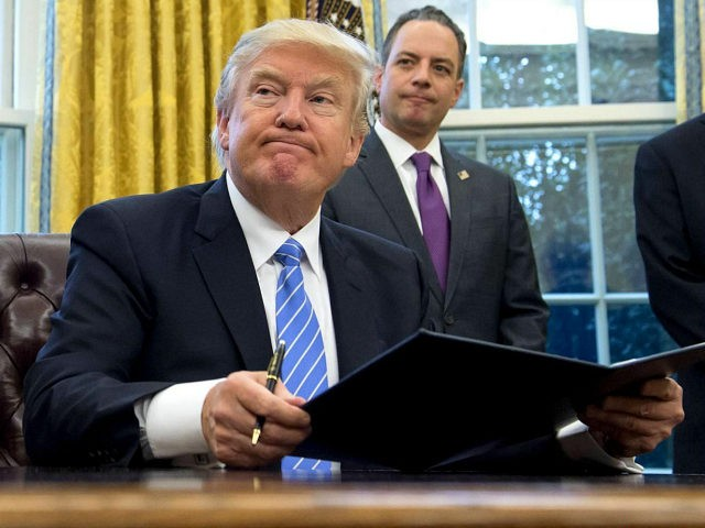 TOPSHOT - US President Donald Trump signs an executive order as Chief of Staff Reince Priebus looks on in the Oval Office of the White House in Washington, DC, January 23, 2017. Trump on Monday signed three orders on withdrawing the US from the Trans-Pacific Partnership trade deal, freezing the hiring of federal workers and hitting foreign NGOs that help with abortion. / AFP / SAUL LOEB (Photo credit should read SAUL LOEB/AFP/Getty Images)