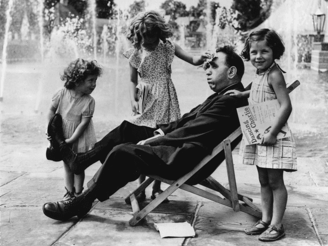 6th August 1951: The three little Robson girls, Hazel, Beryl and Ruth, minister to their tired father, taking off his shoes, mopping sweat from his brow and bringing him games and books. (Photo by Fox Photos/Getty Images)
