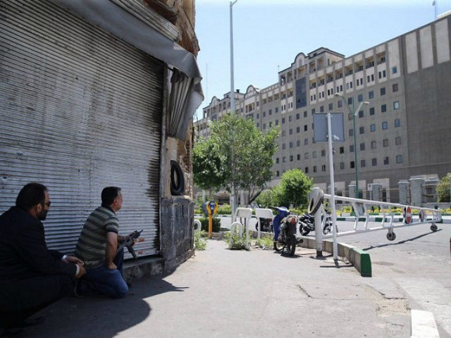 An undercover Iranian policeman (L) holds a weapon outside the Iranian parliament in the capital Tehran on June 7, 2017 during an attack on the complex. The Islamic State group claimed its first attacks in Iran as gunmen and suicide bombers killed at least five people in twin assaults on …