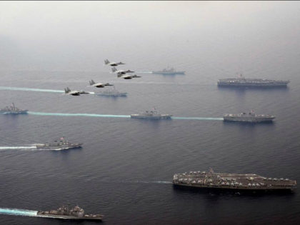 In this Thursday, June 1, 2017 photo released by Japan Air Self-Defense Force, Japan Air Self-Defense Force's F-15 fighter jets fly over U.S. Navy aircraft carriers, USS Ronald Reagan, right bottom, and USS Carl Vinson, right top, Japan Maritime Self Defense Force JS Hyuga, right center, and other vessels during …