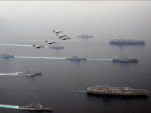 In this Thursday, June 1, 2017 photo released by Japan Air Self-Defense Force, Japan Air Self-Defense Force's F-15 fighter jets fly over U.S. Navy aircraft carriers, USS Ronald Reagan, right bottom, and USS Carl Vinson, right top, Japan Maritime Self Defense Force JS Hyuga, right center, and other vessels during a Japan-U.S. joint training in the Sea of Japan. (Japan Air Self-Defense Force via AP)
