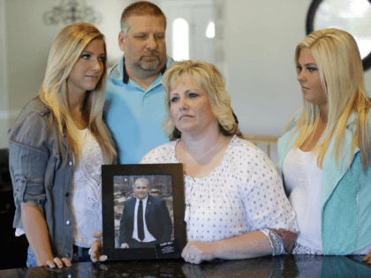 FILE - Laurie Holt holds a photograph of her son Josh Holt, while daughters Jenna, left, Katie, right, and husband Jason look on at her home Wednesday, July 13, 2016, in Riverton, Utah. Josh Holt, an 24-year-old American man jailed in Venezuela has been allowed to meet with U.S. diplomats …