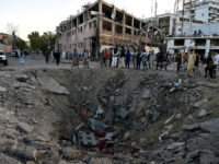 TOPSHOT - Afghan security forces and residents stand near the crater left by a truck bomb attack in Kabul on May 31, 2017. At least 80 people were killed and hundreds wounded May 31 when a massive truck bomb ripped through Kabul's diplomatic quarter, bringing carnage to the streets of …