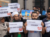 "Muslims hold signs saying ""ISIS WILL LOSE"" and ""#TURNTOLOVE"" on Sunday June 4, 2017 at the police cordon surrounding the site in south London of the deadly van-and-knife attack that killed several people on Saturday night. (AP Photo/Raphael Satter)"