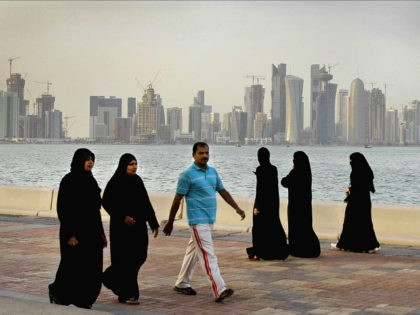 FILE- In this Saturday, April 7, 2012 file photo, the new high-rise buildings of downtown Doha, photographed in the background as Qatari women and a man walk by the sea in Doha, Qatar. Qatar, now facing a diplomatic crisis with other Arab nations, is a small country with a big …