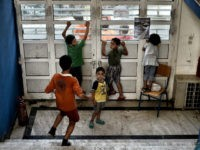 Children stand inside the entrance of an abandoned school used by volunteers for hosting Syrian and Afghan refugees in Athens on July 1, 2016. Some 250 people live in self-management in the school of Athens city center, closed for three years. The families occupy three floors of the building, and …