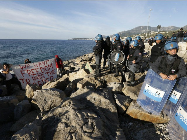 Two migrants hold a banner reading 'We want freedom to pass the border' as they face Italian police officers, on the rocks on the shoreline on September 30, 2015 at the French-Italian border in Ventimiglia. The camp of around 50 people at Ventimiglia -- the town which became a flashpoint …