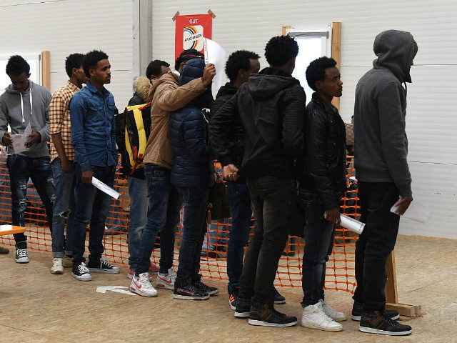 Migrants wait for a first registration at the registration point for asylum seekers in Erding near Munich, southern Germany, on November 15, 2016. The refugees from Eritrea came by plane from Italy. / AFP / CHRISTOF STACHE (Photo credit should read CHRISTOF STACHE/AFP/Getty Images)