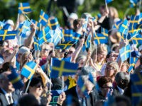 STOCKHOLM, SWEDEN - JUNE 06: Spectators wave the Swedish flag during the national day celebrations at Skansen on June 6, 2017 in Stockholm, Sweden. (Photo by Michael Campanella/Getty Images)