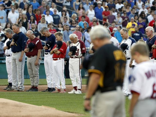 Members of both congressional teams bow their heads for a moment of silence for Rep. Steve Scalise, R-La., before the congressional baseball game Thursday in Washington. alex brandon/Associated Press