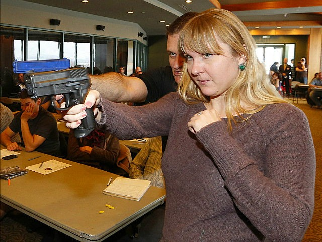 WEST VALLEY CITY, UT - DECEMBER 27: Joanna Baginska (R), a fourth grade teacher at Odyssey Charter School in American Fork, Utah is shown how to handle a 40 cal. Sig Sauer by firearm instructor Clark Aposhian at a concealed-weapons training class to 200 Utah teachers on December 27, 2012 …