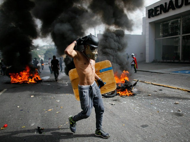 An anti-government demonstrator walks past two National Guard soldiers' motorcycles that were set on fire by protesters when the soldiers ran from their bikes after falling during clashes with protesters in Caracas, Venezuela, Wednesday, May 31, 2017. Protesters have flooded the streets of Venezuela for months, demanding new elections and …