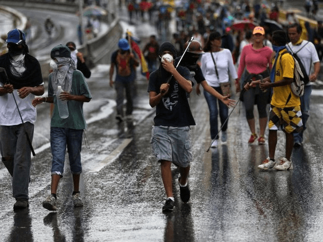 Demonstrators walk under the rain prior clashes with authorities, in Caracas, Venezuela, June 29, 2017. Fernando Llano—AP
