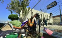 Homeless veteran Kendrick Bailey steps out of his tent on a streetcorner near Skid Row in downtown Los Angeles