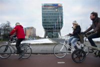 People cycle past the headquarters of the Dutch banking and insurance group ING in Amsterdam on February 13, 2013