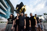 High-profile student campaigner Joshua Wong and a dozen demonstrators attached the black cloth to the giant golden bauhinia flower on Hong Kong's harbourfront in an early morning protest