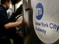 Passengers enter a Metropolitan Transportation Authority (MTA) subway in New York City