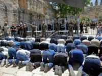 Israeli border police officers stand guard as Muslim men pray outside the Al Aqsa Mosque compound, in Jerusalem Sunday, July 16, 2017. Hundreds of Muslim worshippers visited a Jerusalem holy site Sunday after Israel reopened the compound following a rare closure in response to a deadly shooting last week that …