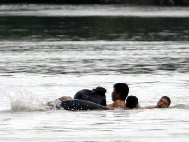 Illegal immigrants use inner-tubes to cross the Rio Grande River at the U.S-Mexico border in Nuevo Laredo, Mexico, just across from Laredo, Texas, Saturday, June 2, 2007. Congressional lawmakers are working on an immigration bill that would legalize millions of unlawful immigrants and beef up border security. (AP Photo/LM Otero)