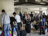Eastern European migrants wait to temporarily settle in a locale in Decines after staying in buildings belonging to the army and the diocese of Lyon, on April 21, 2015.
