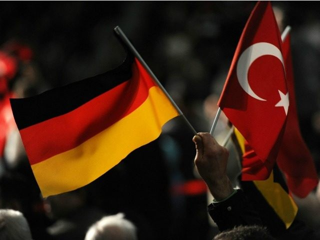A visitor holds a Turkish and a German flag during a Turkish cultural event where Turkish Prime Minister Recep Tayyip Erdogan was expected on February 27, 2011 at the ISS Dome venue in Duesseldorf, western Germany. The event was organised by the Turkish 'Committee for Turks living abroad and related …